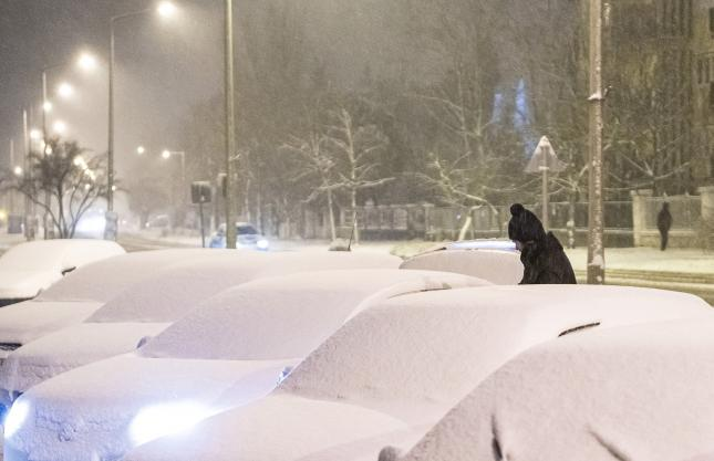 Letakarítja a havat autójáról egy férfi a nyíregyházi Sóstói úton 2021. január 13-án – fotó: MTI/Balázs Attila