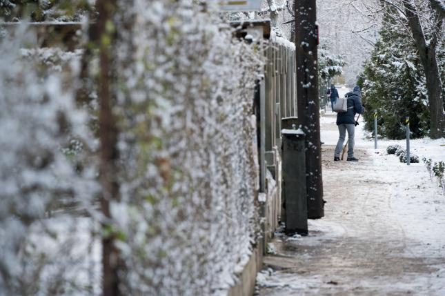 Havat takarít le a járdáról egy nő a behavazott XI. kerületi Bártfai utcában