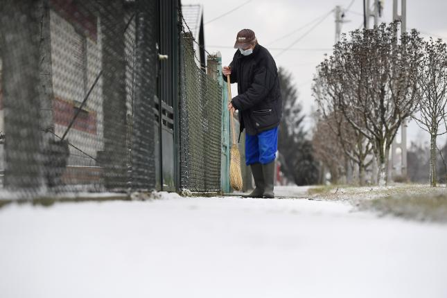 Havat takarít a járdáról egy férfi Gyálon